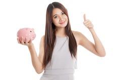 Красивые молодые азиатские большие пальцы руки женщины вверх с копилкой Стоковые Изображения RF