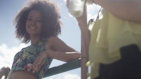 Красивые молодые девушки смешанной гонки говоря около озера и наслаждаясь каникулами Стоковые Изображения RF