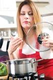 Красивые молодые женщины варя и испытывая еду в kitche Стоковое Фото