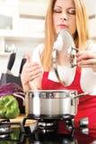 Красивые молодые женщины варя и испытывая еду в kitche Стоковое Изображение RF