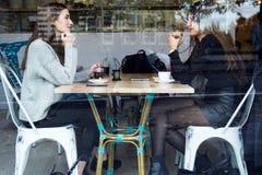 Красивые молодые женщины выпивая чай в кофейне Стоковые Изображения