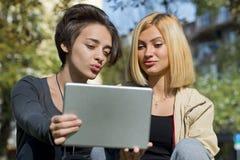 Красивые молодые женщины используя таблетку снаружи Стоковая Фотография