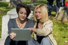 Красивые молодые женщины используя таблетку снаружи Стоковые Изображения
