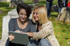 Красивые молодые женщины используя таблетку снаружи Стоковое фото RF
