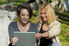 Красивые молодые женщины используя таблетку снаружи Стоковая Фотография RF
