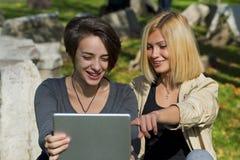 Красивые молодые женщины используя таблетку снаружи Стоковое Изображение