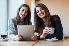 Красивые молодые женщины используя цифровую таблетку в кофейне Стоковые Фото