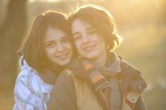 Красивые молодые женщины обнимая снаружи Стоковые Изображения