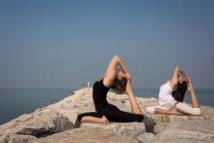 Красивые молодые женщины практикуя йогу Стоковые Изображения