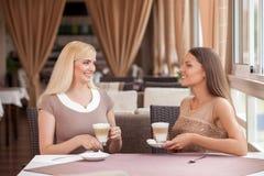 Красивые молодые женщины связывают в кафе Стоковые Изображения RF