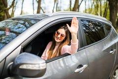 Красивые молодые жизнерадостные женщины смотря камеру с улыбкой и развевая пока сидящ в ее автомобиле Стоковая Фотография