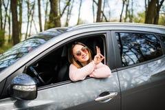 Красивые молодые жизнерадостные женщины смотря камеру с улыбкой и развевая пока сидящ в ее автомобиле Стоковые Фотографии RF