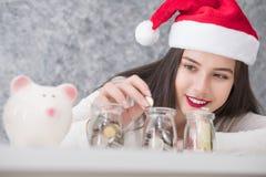 Красивые молодые красивые деньги сбережений девушки на рождество и курортный сезон стоковое изображение