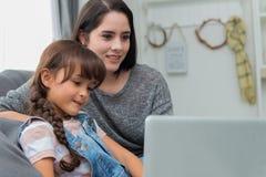 Красивые молодые мама и дочь используют тетрадь на софе на h Стоковые Фотографии RF