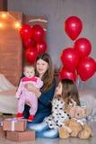 Красивые молодые мать и дочь в платьях с wreathes на их hads с красочными baloons в студии фото стоковое изображение