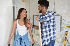 Красивые молодые пары восстанавливая их дом Стоковые Фото