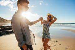 Красивые молодые пары имея потеху на пляже Стоковые Фотографии RF