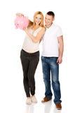 Красивые молодые пары с копилкой Стоковая Фотография