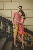 Красивые молодые пары outdoors на винтажных лестницах усмехаясь и обнимая, смотря камеру Стоковое Фото
