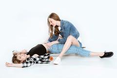 Красивые молодые подруги имея потеху совместно на скейтборде Стоковые Изображения