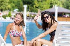 Красивые молодые друзья имея потеху на бассейне стоковые изображения rf
