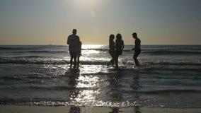 Красивые молодые счастливые люди имея потеху и танцуя в море в замедленном движении сток-видео