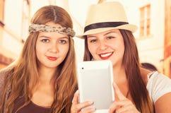 Красивые молодые ультрамодные девушки используя таблетку Стоковое фото RF