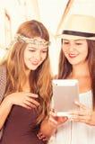Красивые молодые ультрамодные девушки используя таблетку Стоковые Изображения