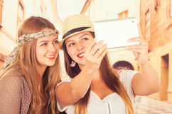 Красивые молодые ультрамодные девушки используя таблетку Стоковые Фотографии RF