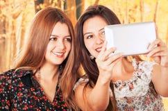 Красивые молодые ультрамодные девушки используя таблетку Стоковая Фотография
