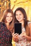 Красивые молодые ультрамодные девушки используя таблетку Стоковые Фото