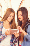 Красивые молодые ультрамодные девушки используя таблетку Стоковая Фотография RF