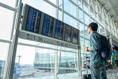 Красивые мужские туристы используют смартфоны к проверочным полетам перед восхождением на борт Польза концепции перемещения техно стоковое фото rf