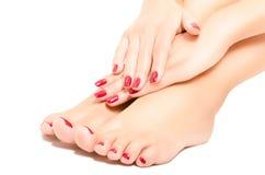 Красивые нога и руки с красным маникюром Стоковая Фотография