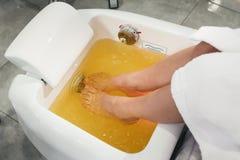 Красивые ноги девушки в белом купальном халате Самомоднейший салон красотки Стоковое Изображение