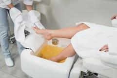 Красивые ноги девушки в белом купальном халате Самомоднейший салон красотки Стоковая Фотография RF