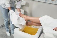 Красивые ноги девушки в белом купальном халате Самомоднейший салон красотки Стоковые Изображения
