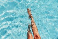 Красивые ноги женщины брызгая в бассейне Стоковое фото RF