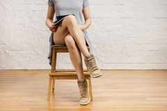 Красивые ноги женщины читая газету Стоковые Фотографии RF