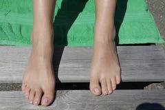 Красивые ноги туристов на пляже стоковое изображение