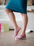 Красивые ноги ` s женщины нося сезонные розовые ботинки на предпосылке магазина Ботинки покупок девушки моды в магазине Стоковое фото RF