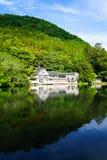Красивые обильные естественные тени весны зеленеют отражение зеркала предпосылки горы на свежем озере Kinrinko с зданиями Стоковое Изображение RF