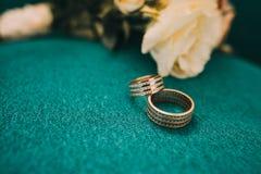 Красивые обручальные кольца лежат на деревянной поверхности на фоне букета цветков Стоковое Изображение RF