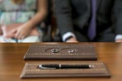 Красивые обручальные кольца лежат на деревянной поверхности на фоне пар свадьбы Стоковые Изображения