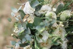 Красивые обручальные кольца на букете белых роз Стоковые Изображения