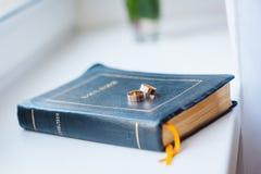 Красивые обручальные кольца на голубой закладке библии Стоковые Изображения RF
