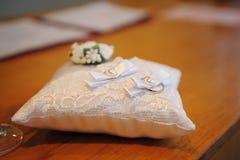Красивые обручальные кольца на подушке кольца более чуть-чуть Стоковое фото RF