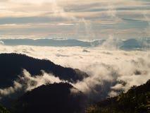 Красивые облака в небе формируют верхнюю часть горы Стоковая Фотография