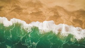 Красивые океанские волны и брызгают на песчаном пляже в Nazar, Португалии вид с воздуха Стоковая Фотография RF