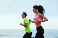 Красивые пары бежать вокруг в свежем воздухе на пляже Стоковое Изображение